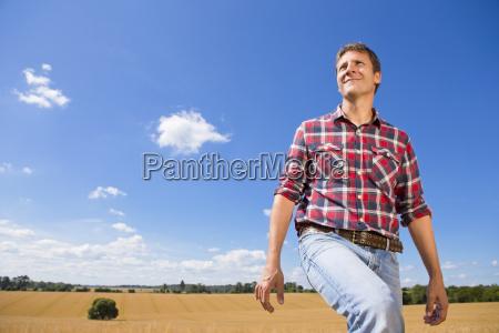 smiling farmer walking in sunny rural