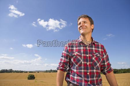 smiling farmer in sunny rural barley