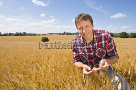 portrait smiling farmer examining sunny rural