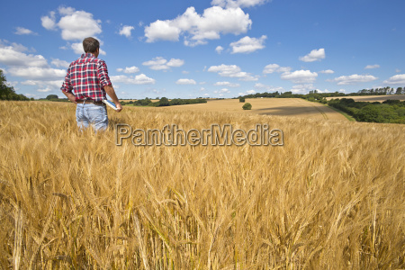 farmer with digital tablet looking out