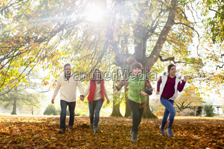 happy family running through autumnal forest