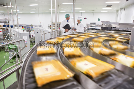 workers talking behind packages of cheese
