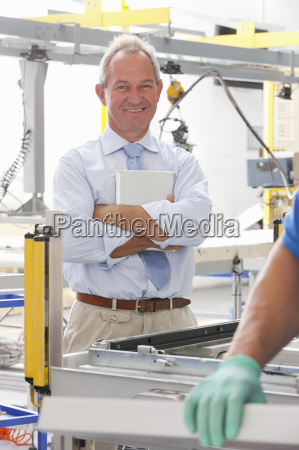 businessman supervising worker and smiling at