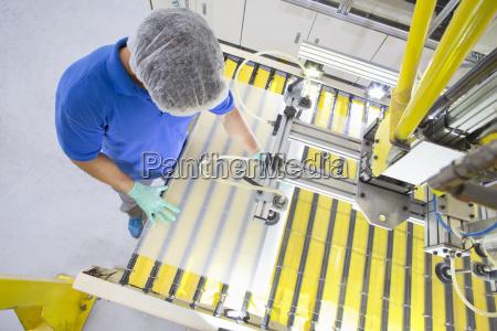 factory floor worker coating glass for