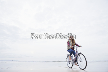 portrait woman riding bicycle on beach
