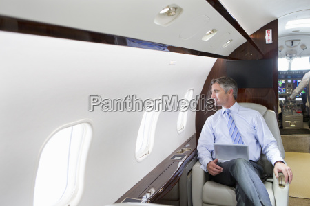 businessman with digital tablet looking out