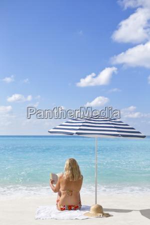 woman reading book on sunny beach