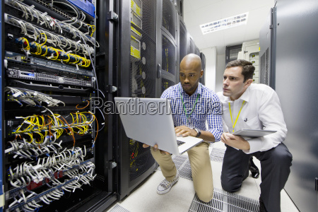 technicians with laptop checking server in