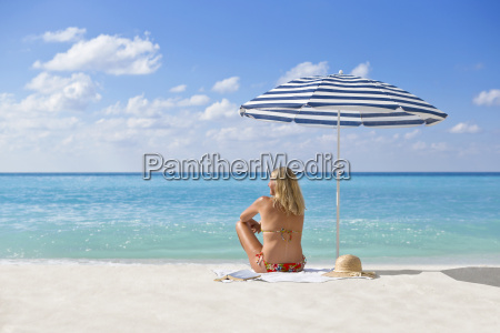 woman relaxing on sunny beach under