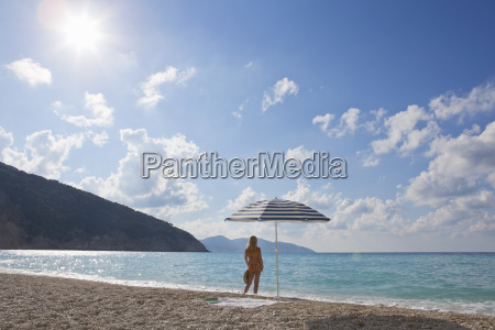 woman standing on sunny beach looking