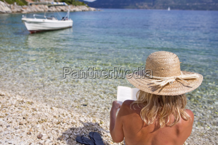 woman in sun hat reading book