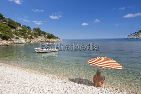 woman sitting under striped beach umbrella