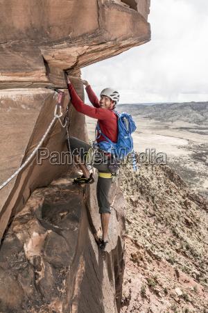a man rock climbing a desert