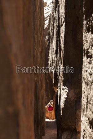 a woman hikes through a slot