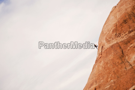 a woman climbs a cliff near
