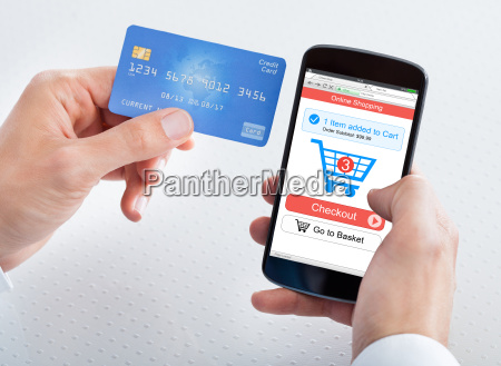 man holding credit card and cell