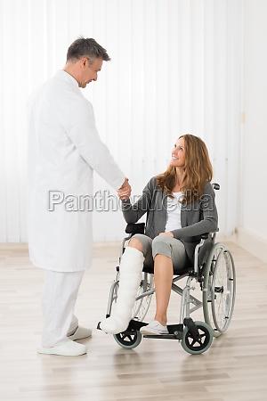 arzt schuettelt haende mit patient