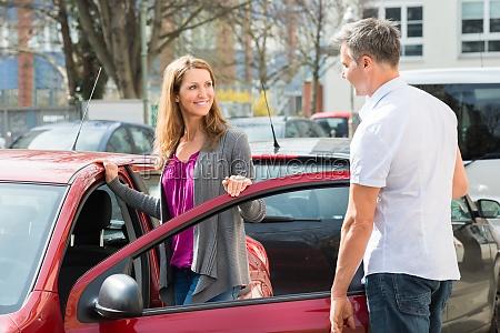 couple standing by new car door