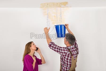 worker sammeln von wasser in eimer
