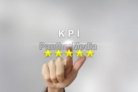 business hand pushing kpi or key
