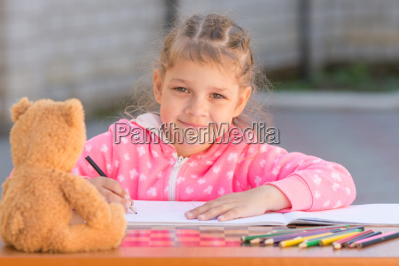 girl draws with crayons and smile