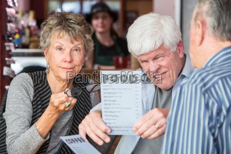 mature man trying to read menu