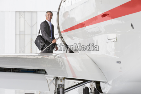 businessman boarding private jet and smiling