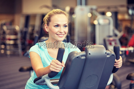 smiling woman exercising on exercise bike