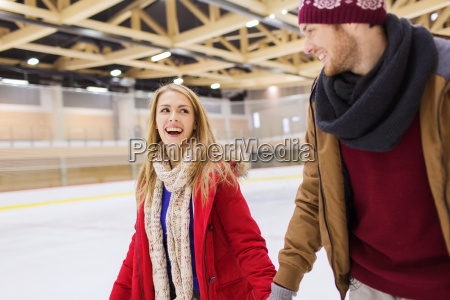 happy couple holding hands on skating