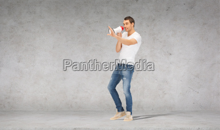 handsome man with megaphone over concrete