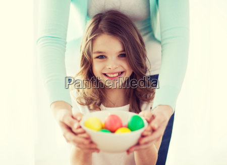 smiling girl and mother holding colored