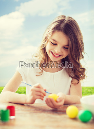 smiling little girl coloring eggs for