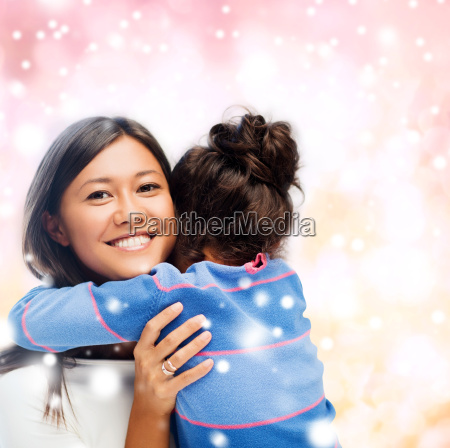 smiling little girl and mother hugging