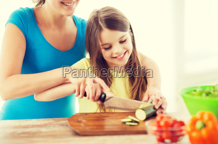 smiling little girl with mother chopping