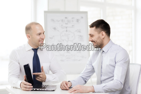 two smiling businessmen with laptop in