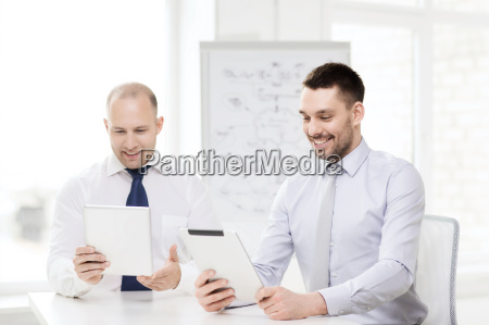 two smiling businessmen with tablet pc