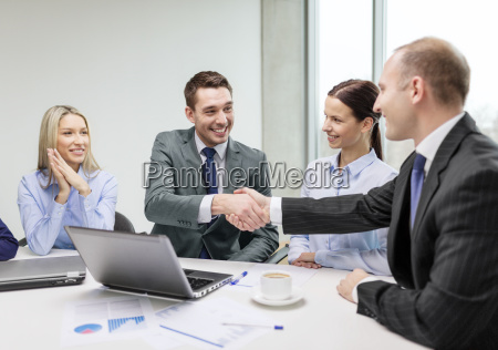 two businessman shaking hands in office