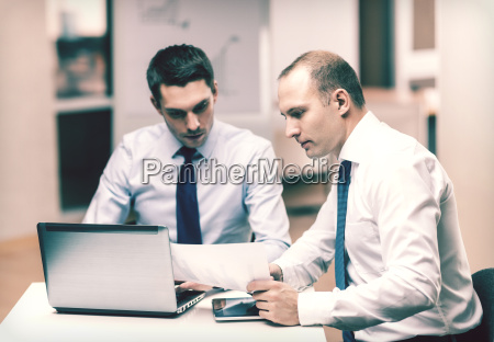 two businessmen having discussion in office