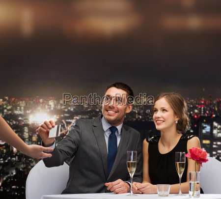 smiling couple paying for dinner with