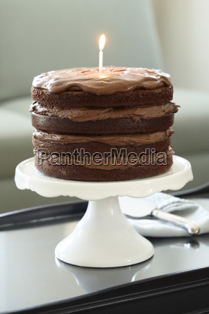 layered chocolate birthday cake with lit