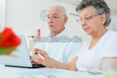 elderly couple on computer wife holding