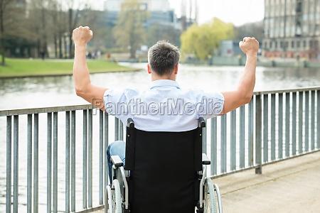 behinderter mann auf rollstuhl mit hand