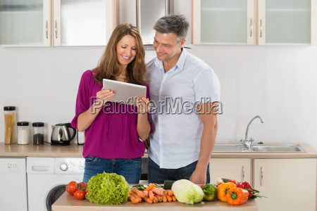 couple looking at recipe on digital