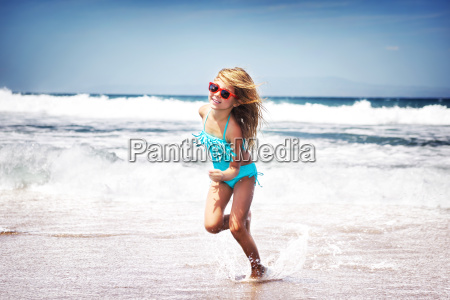 baby girl running on a beach