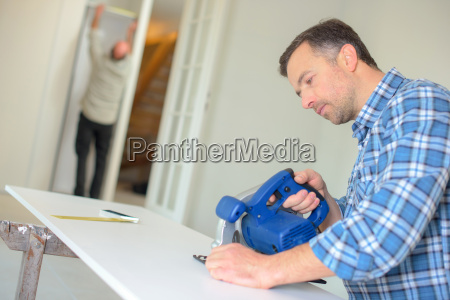 carpenter using band saw to cut
