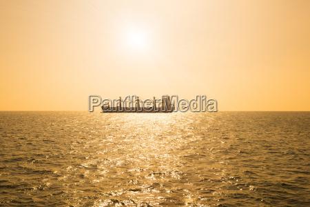 silhouette of cargo ship on ocean