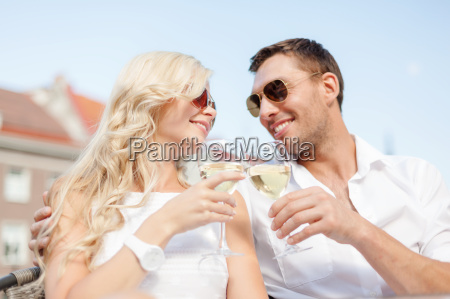 smiling couple in sunglasses drinking wine