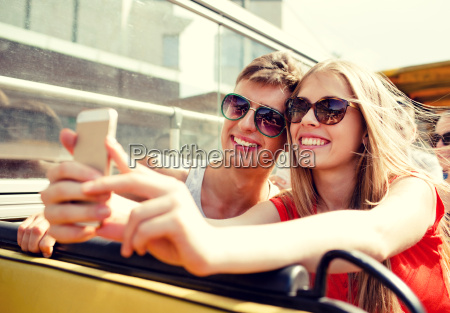 smiling couple with smartphone making selfie