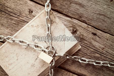 gekettetes buch auf holzhintergrund