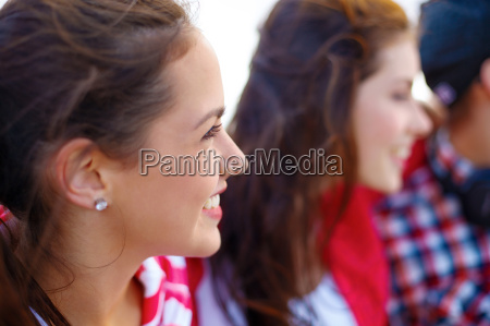 smiling teenage girl outdoors with friends